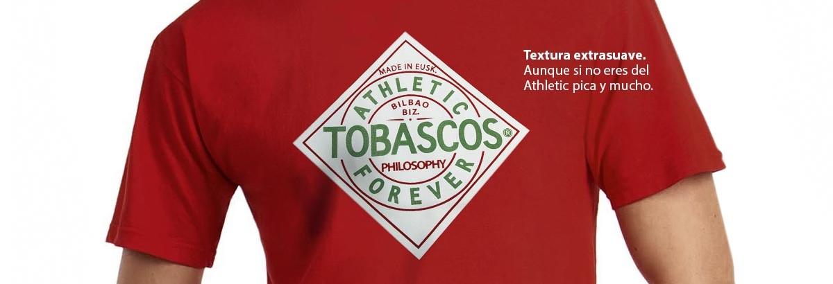 Camiseta roja de algodón de altísima calidad con serigrafía a dos colores. La serigrafía es una versión de la famosa etiqueta de Tabasco adaptada a la idiosincrasia de nuestro Athletic: TOBASCOS. Una filosofía única en el mundo del futbol. Un equipo especial que sólo se nutre de jugadores nacidos o formados en la cantera vasca.
